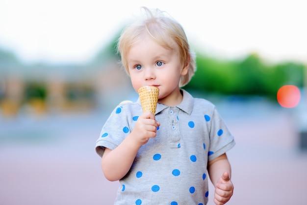 Menino bonito da criança comendo sorvete ao ar livre