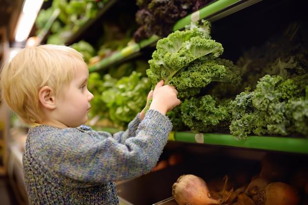 Menino bonito da criança em uma despensa ou em um supermercado que escolhe a salada orgânica fresca da couve.