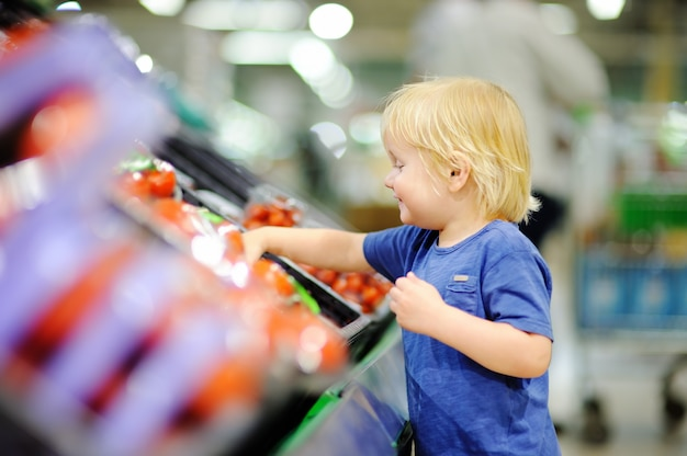 Menino bonito da criança em uma despensa ou em um supermercado que escolhe tomates frescos. estilo de vida saudável para a família jovem com crianças