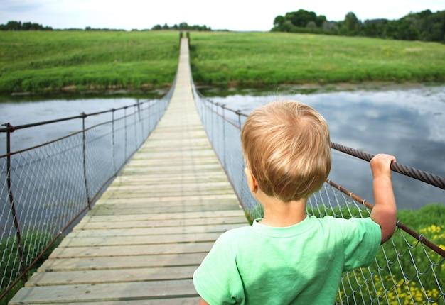 Menino bonito da criança em uma ponte de suspensão através do rio. viagem de aventura, olhe para o futuro, abrindo um novo conceito de caminho