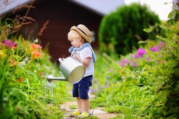 Menino bonito da criança no chapéu de palha regar plantas no jardim em dia ensolarado de verão