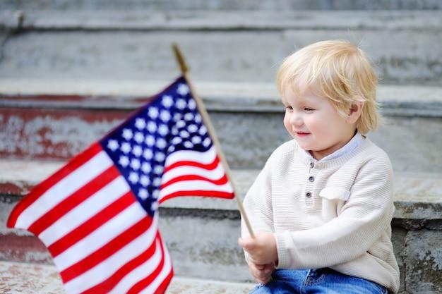 Menino bonito da criança que guarda a bandeira americana. conceito do dia da independência.
