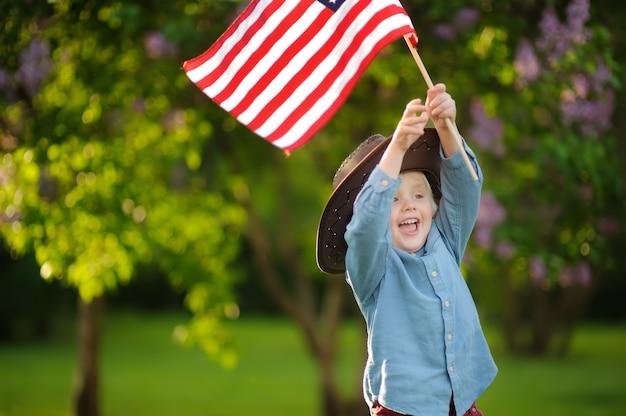 Menino bonito da criança que guarda a bandeira americana no parque bonito.