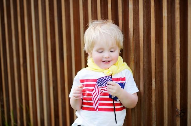 Menino bonito da criança que guarda a bandeira americana.