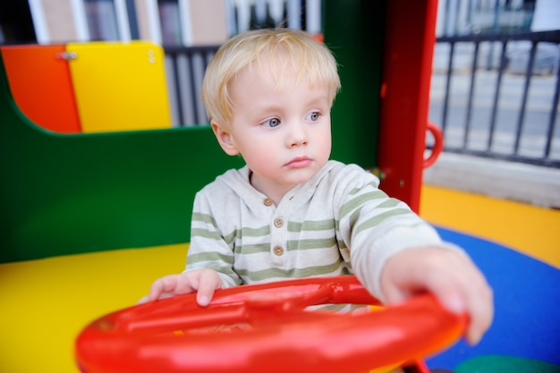 Menino bonito da criança que tem o divertimento no campo de jogos. ativo jogo ao ar livre para crianças pequenas