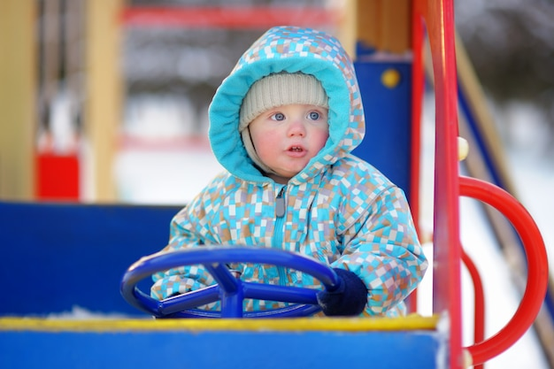 Menino bonito da criança se divertindo no playground