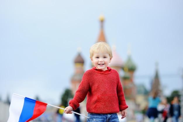 Menino bonito da criança segurando a bandeira russa com a red square e vasilevsky descida