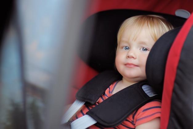 Menino bonito da criança sentada no banco do carro