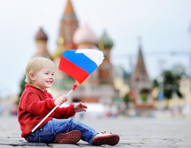 Menino bonito da criança sentado e jogando com a bandeira russa com a red square e vasilevsky descida