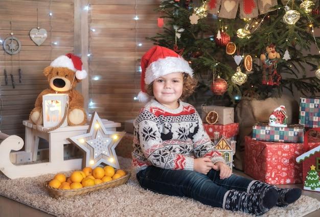 Menino bonito de cabelos encaracolados em um chapéu de papai noel vermelho para a árvore de natal. conceito de natal e ano novo