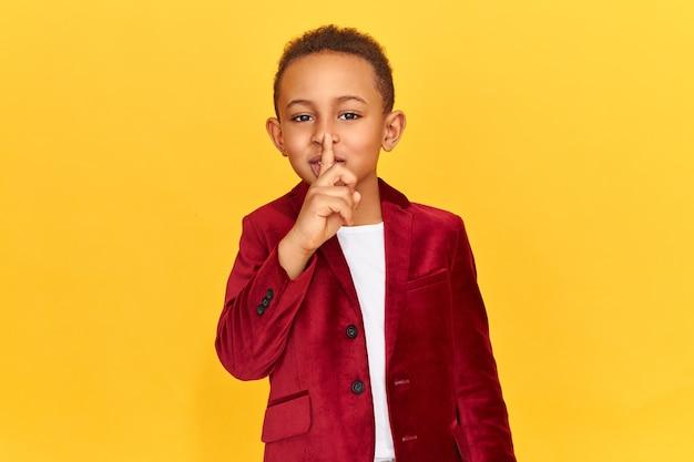 Menino bonito de pele escura fazendo gesto de conspiração, mantendo o dedo indicador nos lábios.