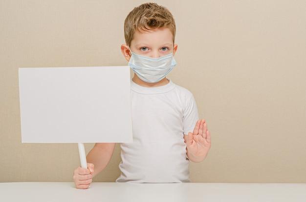 Menino bonito de quatro anos de idade em uma máscara médica e um sinal em branco