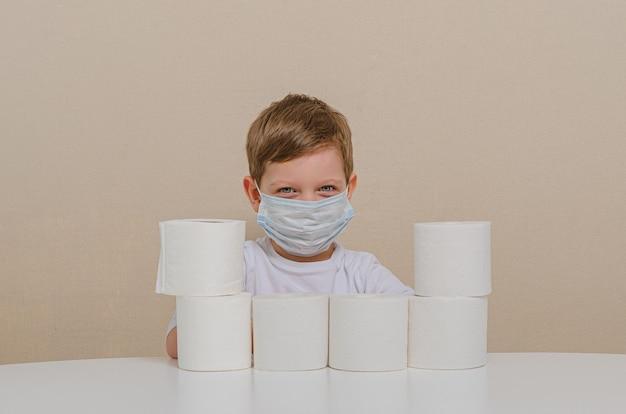 Menino bonito de quatro em uma máscara médica protetora brinca com papel higiênico - constrói uma parede protetora. quarentena em casa com crianças, lazer em família.