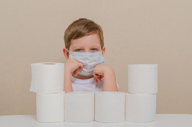 Menino bonito de quatro em uma máscara médica protetora brinca com papel higiênico