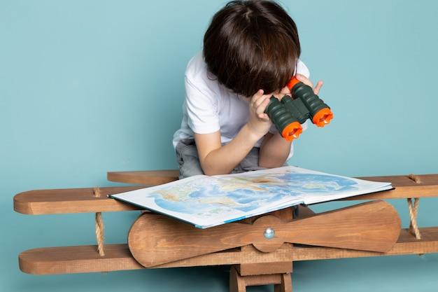 Menino bonito de vista frontal em camiseta branca, olhando através do mapa no chão azul