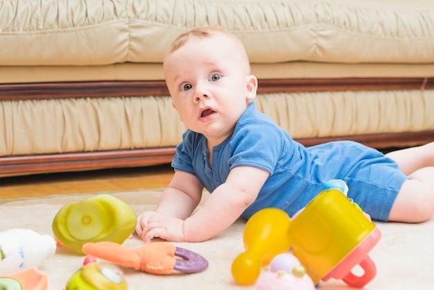 Menino bonito, deitado no tapete com brinquedos