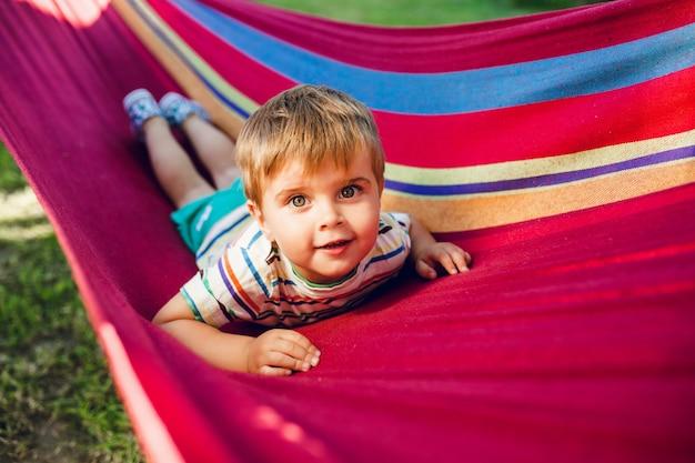 Menino bonito descansando em uma rede brilhante e parece relaxado.