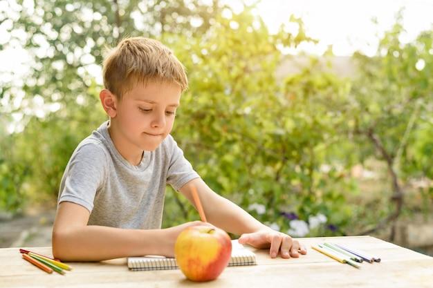 Menino bonito desenha com lápis ainda vida. ar livre. jardim no. criativo .