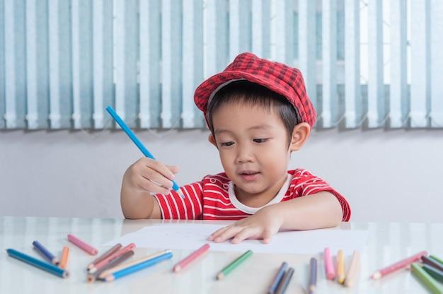 Menino bonito desenha com lápis de cor no quarto das crianças