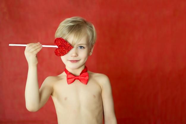 Menino bonito do cupido com um sorriso triplo, um laço e uma seta do coração isolados na parede vermelha. conceito dia dos namorados