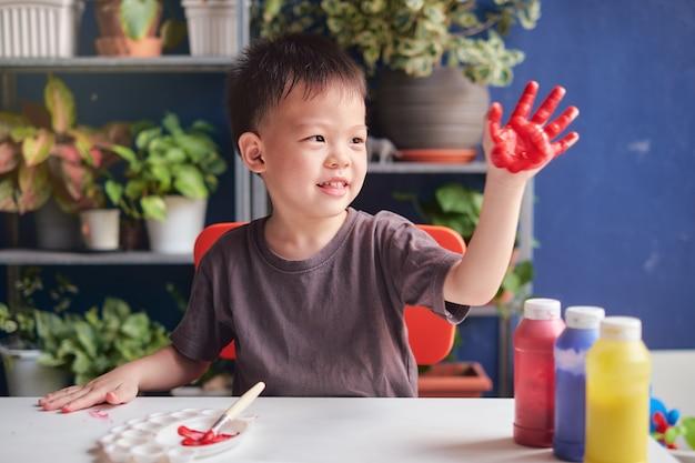Menino bonito do jardim de infância asiático de 4 anos pintando a dedo com as mãos e aquarelas