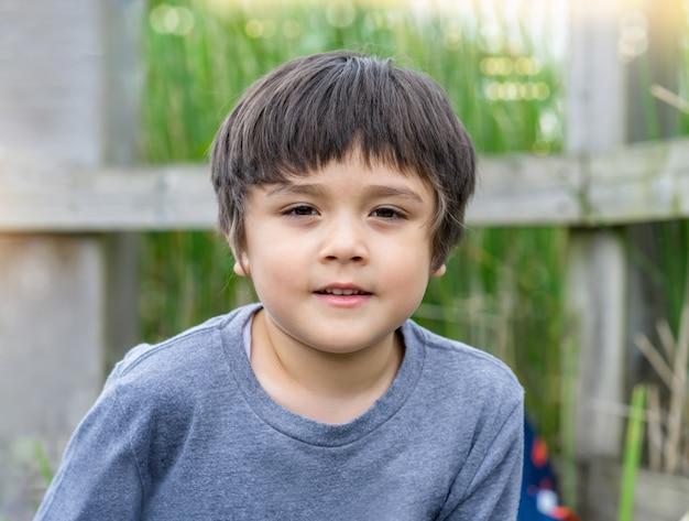 Menino bonito do retrato ao ar livre, olhando para a câmera com uma cara sorridente.