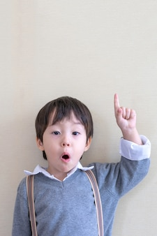 Menino bonito do retrato que aponta o dedo para cima no branco