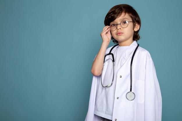 Menino bonito doce criança adorável menino de terno médico branco e óculos de sol na mesa azul