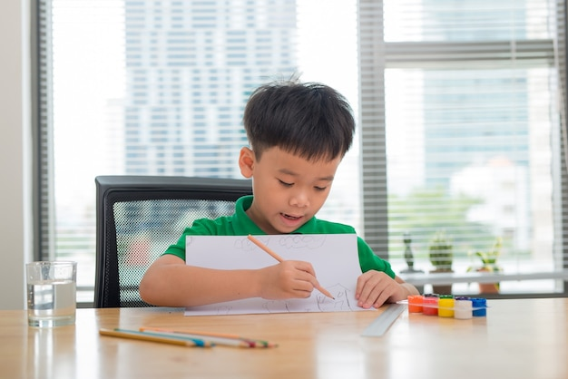 Menino bonito e confuso e sorridente fazendo lição de casa, colorir, escrever e pintar. crianças pintam. crianças desenham. pré-escolar com livros na biblioteca. lápis coloridos e papel sobre uma mesa. menino criativo.