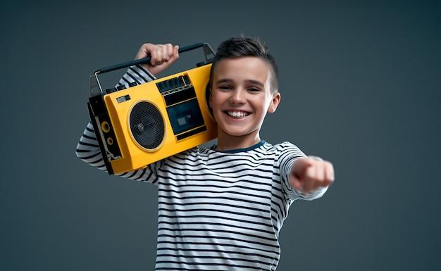 Menino bonito e elegante com um suéter listrado com um gravador retrô amarelo mostra um dedo para a câmera isolada em um cinza.