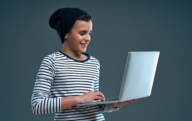 Menino bonito e elegante com um suéter listrado e um chapéu com um laptop na mão isolado em um cinza.