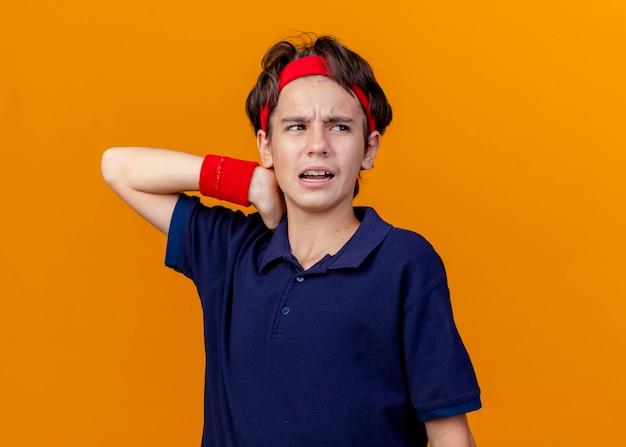 Menino bonito e esportivo dolorido usando bandana e pulseiras com aparelho dentário, olhando para o lado, mantendo a mão atrás do pescoço isolada na parede laranja com espaço de cópia