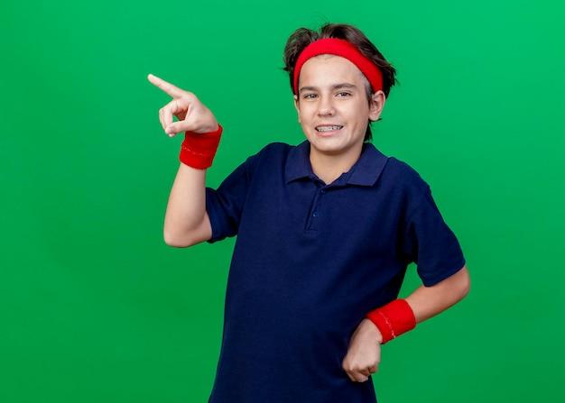 Menino bonito e esportivo sorridente, usando bandana e pulseiras com aparelho dentário, mantendo a mão na cintura, olhando para frente, apontando para o lado isolado na parede verde com espaço de cópia