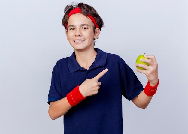 Menino bonito e esportivo sorridente, usando bandana e pulseiras com aparelho dentário, olhando para a frente, segurando e apontando para uma maçã isolada na parede branca
