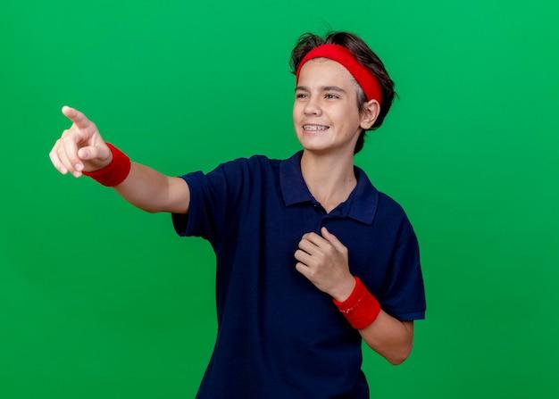 Menino bonito e esportivo sorridente, usando bandana e pulseiras com aparelho dentário tocando o peito, olhando e apontando para o lado isolado na parede verde com espaço de cópia