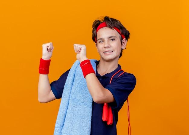 Menino bonito e esportivo sorridente usando bandana e pulseiras com toalha e pular corda nos ombros, apontando para trás, isolado