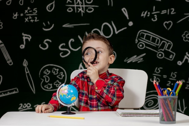 Menino bonito e inteligente está sentado em uma mesa com uma lupa na mão. a criança está lendo um livro com um quadro negro em um fundo. pronto para a escola. de volta à escola.