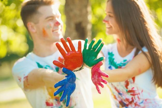 Menino bonito e menina que agitam suas mãos ou palmes pintadas na câmera e no sorriso. na frente da câmera em foco, há um plano multicolorido das mãos do casal apaixonado.