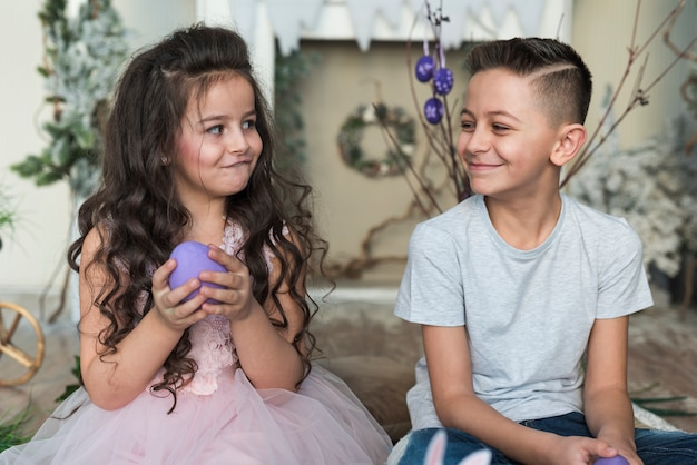 Menino bonito e menina sentada com ovos de páscoa