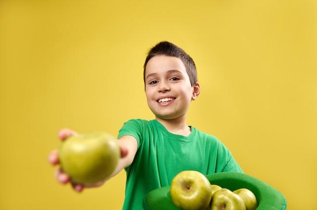 Menino bonito e sorridente com um chapéu verde de duende irlandês cheio de maçãs nas mãos e mostra uma maçã verde para a câmera