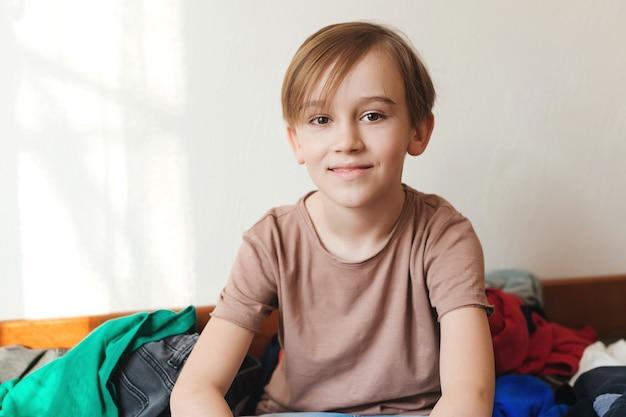 Menino bonito e sorridente. menino sentado na cama com muitas roupas espalhadas.