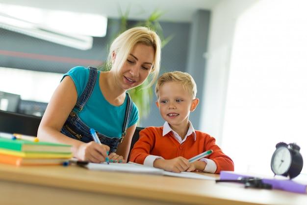 Menino bonito e sua mãe sentar na mesa no escritório e desenhar