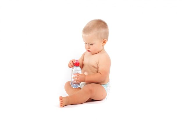 Menino bonito em fraldas com garrafa de água