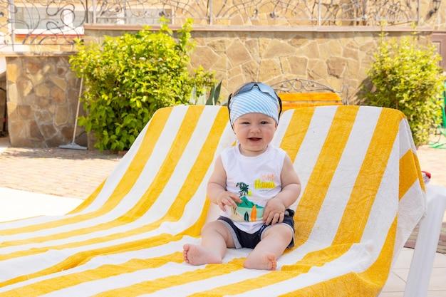 Menino bonito em óculos de sol e uma bandana senta-se em uma espreguiçadeira à beira da piscina. foco seletivo.