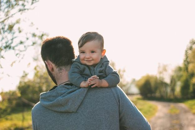 Menino bonito em seus ombros de pai andando na estrada ao ar livre, sensibilidade ao conceito de natureza