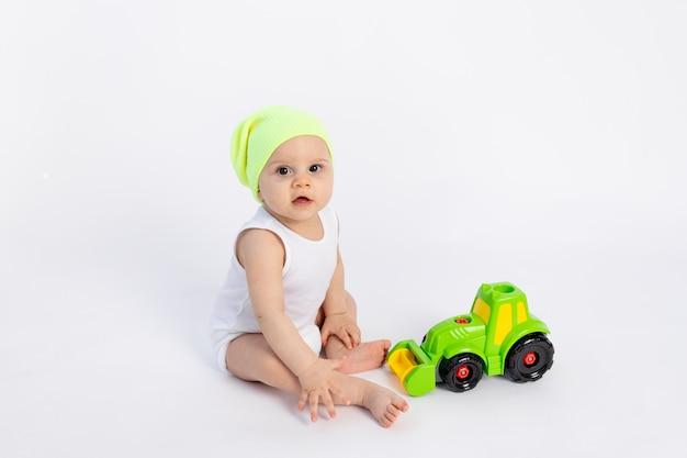 Menino bonito em uma roupa branca em uma parede branca isolada, brincando com uma máquina de escrever, desenvolvimento inicial de crianças, bebê 8 meses entre brinquedos,