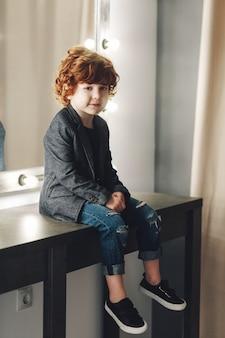 Menino bonito encaracolado na jaqueta e jeans rasgados posando perto do espelho e sorrindo
