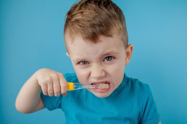 Menino bonito, escovando os dentes na parede azul