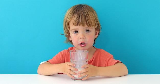 Menino bonito está bebendo leite