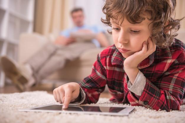 Menino bonito está jogando com tablet em casa.